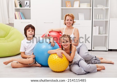 Woman and kids ready for gymnastic - sitting on the floor with large exercise balls - stock photo