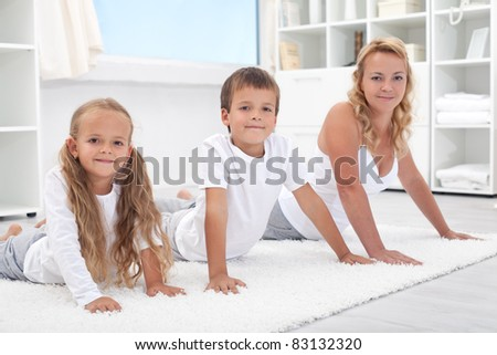 Woman and kids stretching their backs doing gymnastic exercises at home - focus on the boy - stock photo