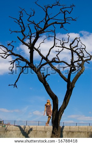 Woman and leafless dry tree - stock photo