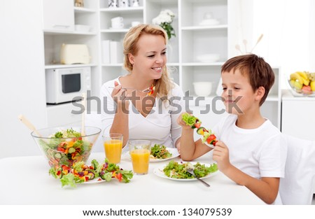 Woman and little boy having a healthy salad for snack - stock photo
