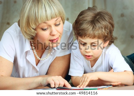 woman and little boy lying down on the floor and reading a book