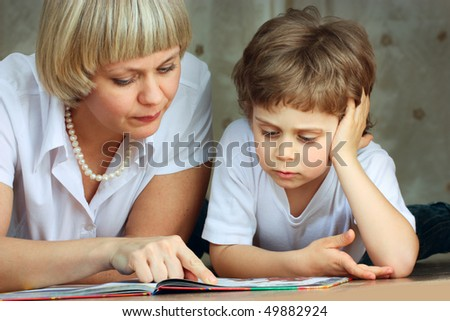 woman and little boy lying down on the floor and reading a book - stock photo