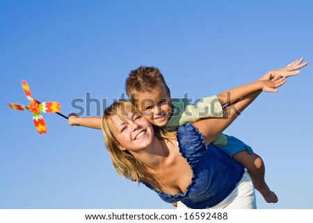 Woman and little boy playing airplane with a pinwheel against blue summer sky - stock photo