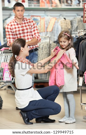 woman and little girl choosing and trying on raincoat during shopping at outerwear supermarket - stock photo