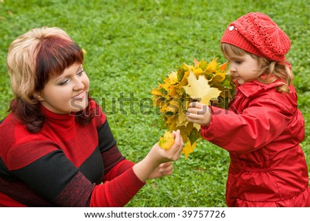 woman and  little girl collect maple leafs In park in autumn - stock photo