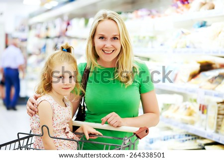 woman and little girl during shopping at fruit vegetable supermarket - stock photo