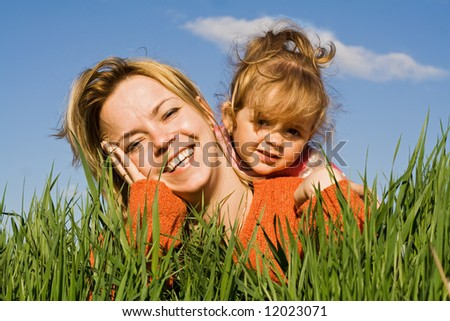 Woman and little girl having fun in the grass - stock photo