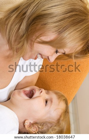 Woman and little girl laughing and playing - stock photo