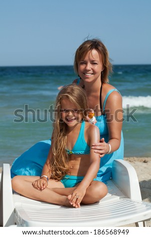Woman and little girl using sunscreen cream - sitting on a beach chair - stock photo