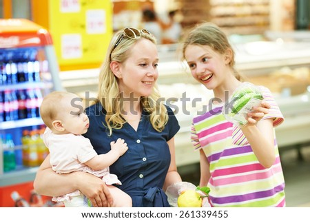 woman and little girls during family shopping at fruit vegetable supermarket
