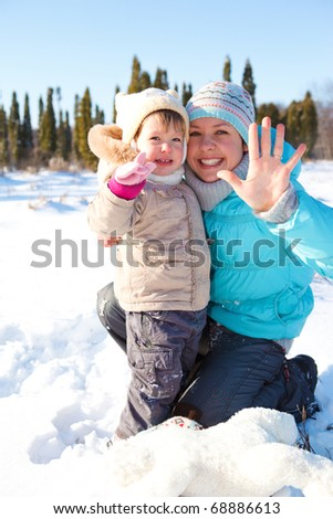 Woman and lovely toddler girl together in snow - stock photo