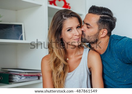 Woman and man are posing to photo while man is kissing on the cheek of woman. Bedroom background.