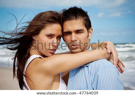 Woman and man at the beach, looking into camera - stock photo