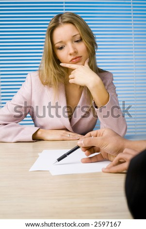 Woman and man at the office desk. Man explains something - only his hands visable. Woman's thinking. - stock photo