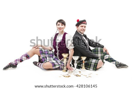Woman and man dancing Scottish dance with cups and medals