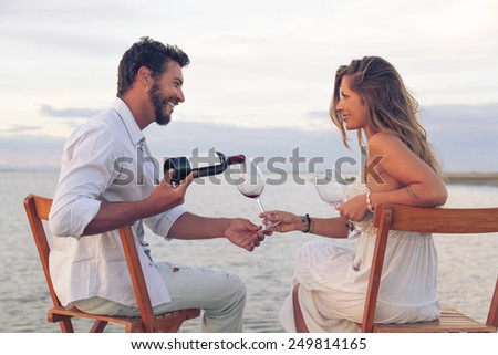 Woman and man drinking red wine at the seaside - stock photo