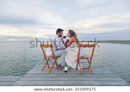 Woman and man drinking red wine at the seaside