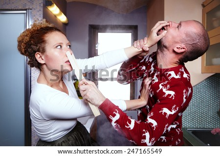 Woman and man fighting in kitchen with tools - stock photo