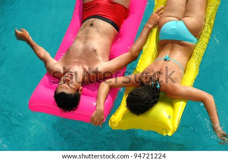 Woman and man floating in water pool - stock photo