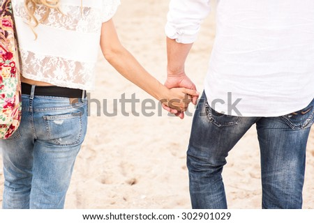 Woman and man holding hands walking on the beach - stock photo