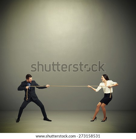 woman and man in formal wear pulling the rope over dark grey background - stock photo