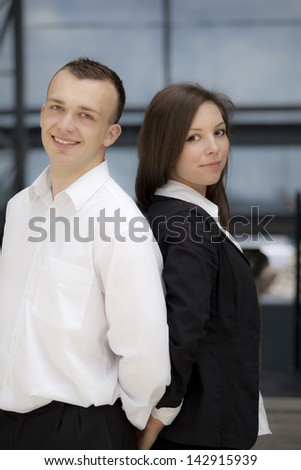 Woman and man in suit standing in front of a building. Background is out of focus.