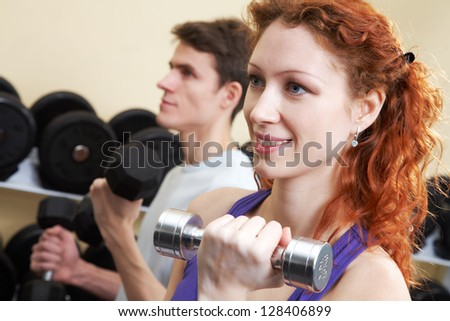 Woman and man lifting dumbbells doing biceps workout - stock photo
