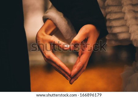 woman and man making heart with hands - stock photo
