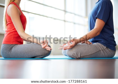 Woman and man meditating face to face - stock photo