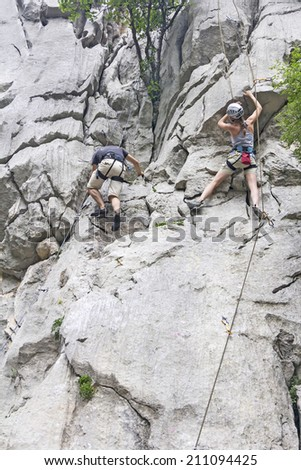Woman and man rock climbing on a high rock wall  - stock photo