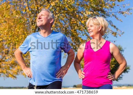Woman and man, seniors, doing sport outdoors in the grass on meadow