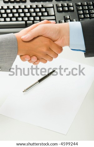 Woman and man shaking hands over blank paper and pen, keyboard on the background
