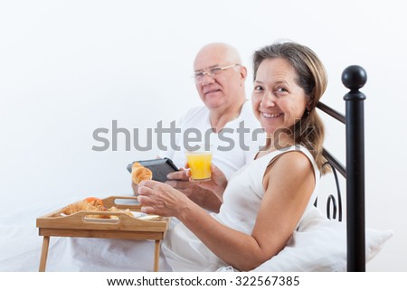 Woman and man sitting on  white bed near tray with breakfast . - stock photo