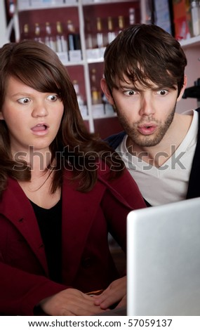 Woman and man staring in disbelief at a laptop - stock photo