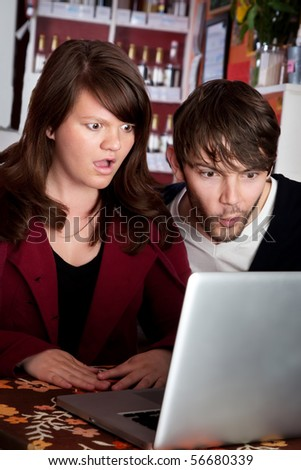 Woman and man staring with shock at laptop computer - stock photo