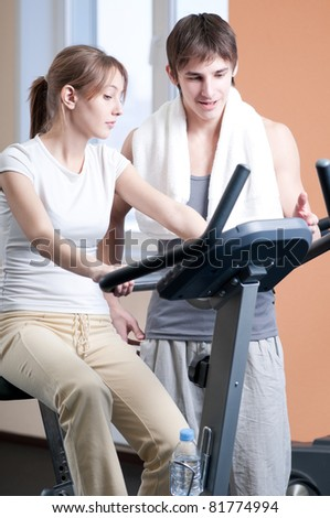 Woman and man train on machine in a gym assisted by personal instructor - stock photo