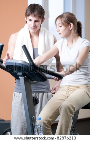 Woman and man train on machine in a gym assisted by personal instructor
