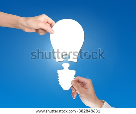 Woman and man two hands assembling one bulb shape puzzle of two jigsaw pieces, isolated on white. - stock photo