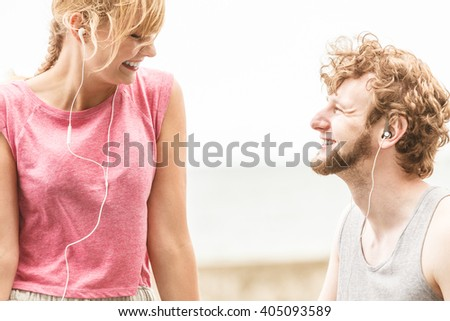 Woman and man with earphones listening to music outdoor. Young couple relaxing taking break from fitness exercise. Healthy lifestyle.