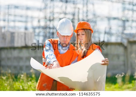 woman and man working as architects on a construction site - stock photo