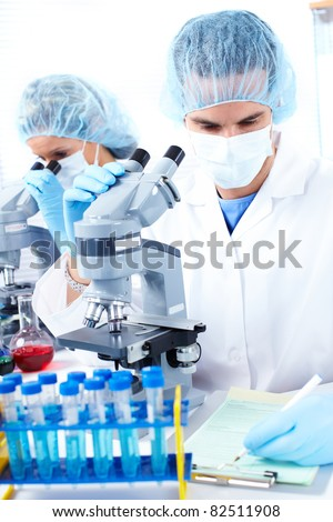 Woman and man working with a microscope in laboratory. - stock photo