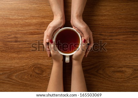 Woman and mens hands holding hot cup of tea on wooden table - stock photo
