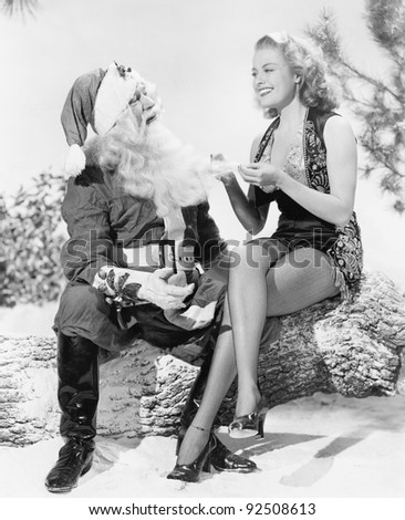 Woman and Santa Claus sitting together laughing