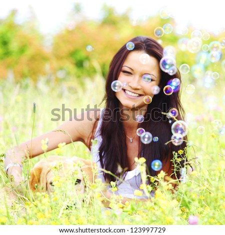 woman and she lablador dog in green grass - stock photo