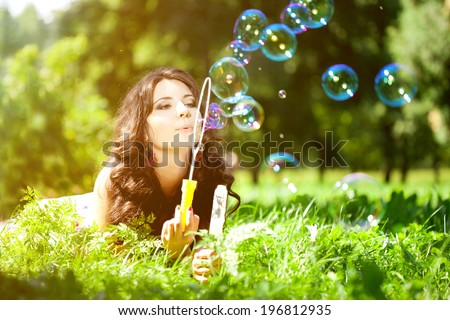 Woman and soap bubbles in park. Beautiful young girl lying on the grass in the field. Smiling trendy stylish woman on nature