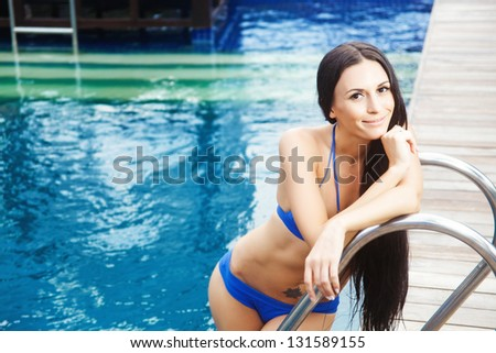 woman and swimming pool at resort - stock photo