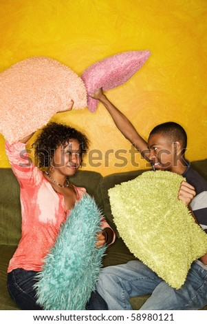 Woman and teen boy have pillow fight on green sofa - stock photo