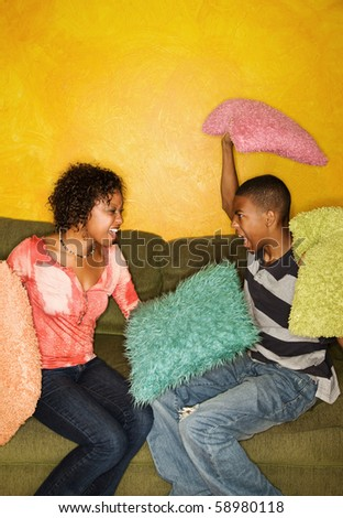 Woman and teenage boy have pillow fight on green sofa - stock photo