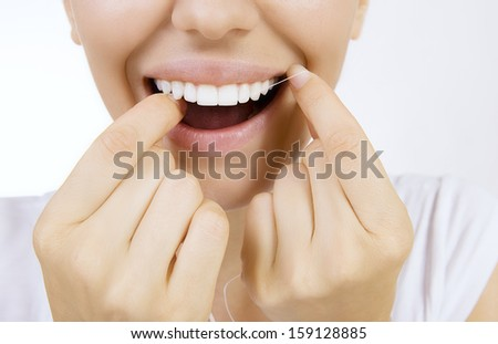 Woman and teeth floss - Young caucasian woman flossing her teeth (close up woman smile) - stock photo