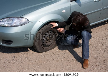 woman and the car with punctured wheel - stock photo